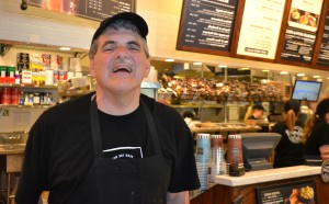 A Woods resident smiles during his shift at Corner Bakery Cafe.