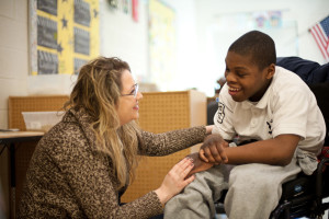 A Woods teacher smiles and talks with a Woods student.