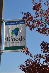 A flag celebrating Woods Services Centennial hangs outside.
