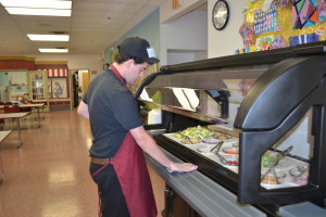 A Common Grounds Cafe employee oversees the salad bar.
