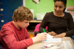 A Woods Services student works with a teacher.