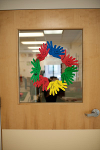 Hands cut out of construction paper form a circle on a classroom door at Woods Services.