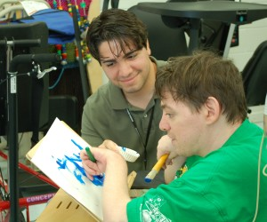 A Woods teacher smiles as a Woods resident does a painting.