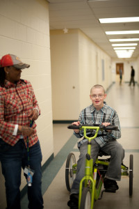 A Woods resident rides a bike for physical therapy while a therapist looks on.